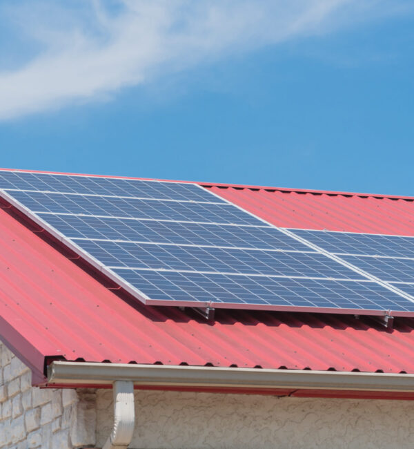 Close-up solar panel on metal roof of commercial building at Gainesville, TX, USA. Photovoltaic solar collector on classic rib steel tile floor. Renewable clean green energy, sustainable economy