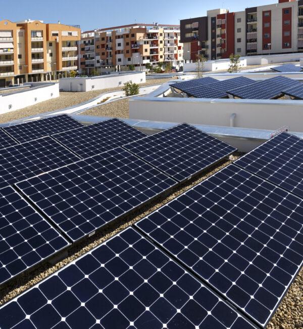Pannelli fotovoltaici sopra il tetto di un palazzo, intorno altri palazzi